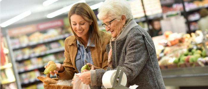 dos mujeres una joven y otra adulto mayor de compras en el supermercado comprando fruta