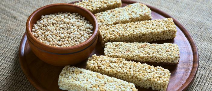 seis barritas de amaranto en un plato de barro y taza de barro con granos de amaranto