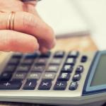 mano con anillo en el dedo usando calculadora para solicitar un credito para pensionados