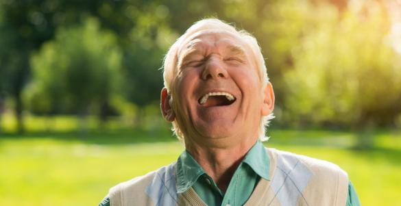 hombre mayor riendo en un parque el conoce el beneficio de la risa terapia en la salud