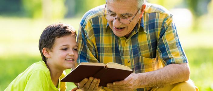 abuelo y nieto sentados en el parque leyendo un libro de tapa color cafe