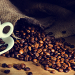 taza blanca con cafe liquido en su interior y al lado un costal de granos de cafe
