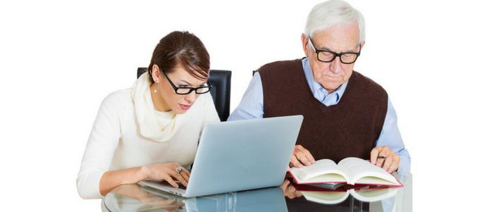 mujer joven con laptop a su lado adulto mayor de lentes leyendo libro para aprender idiomas