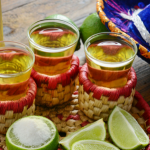 botella de tequila caballitos servidos limones sal y sombrero de charro bebidas mexicanas
