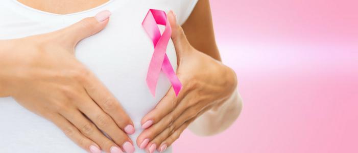 mujer de blusa blanca tocando su pecho con liston rosa por el dia mundial contra el cancer de mama