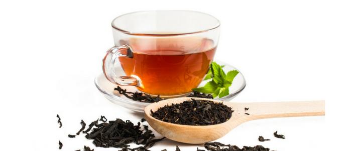 taza de cristal y cuchara con té negro en ellas conoce los beneficios del te negro