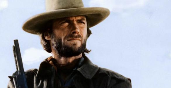 personaje de una pelicula de clint eastwood con camisa escopeta barba y sombrero