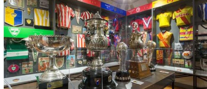 5 trofeos en vitrinas de cristal junto con playeras de diferentes equipos de futbol