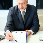 asesor financiero de traje y corbata mostrando un documento a dos personas hombre y mujer