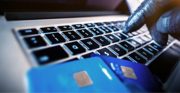 teclado de computadora mano con guante negro y dos tarjetas de credito practica de fraude