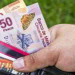 mano tomando cartera negra con diferentes tarjetas y billetes de diferentes denominaciones