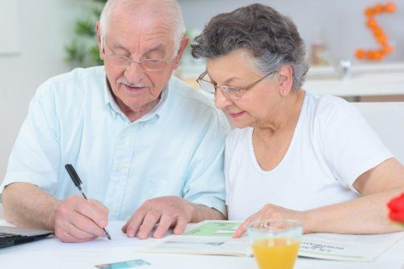 par de adultos mayores con pluma y papales sobre la mesa