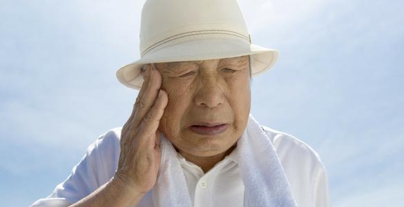 adulto mayor de sombrero blanco y mano en la cabeza mira consejos contra el golpe de calor