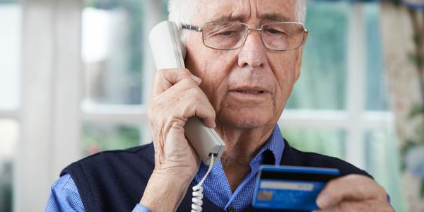 adulto mayor canoso y de lentes al telefono con su tarjeta de credito en la mano