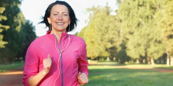 mujer de sudadera rosa y audifonos sonriendo corriendo en un parque con arboles