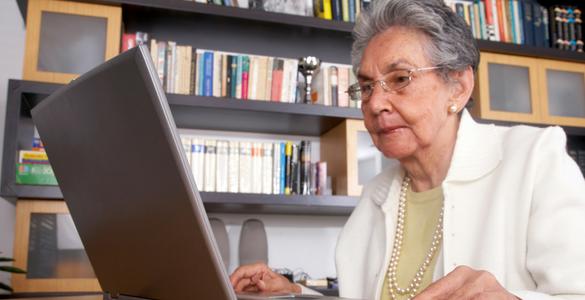 mujer mayor de lentes y sueter blanco frente a una computadora