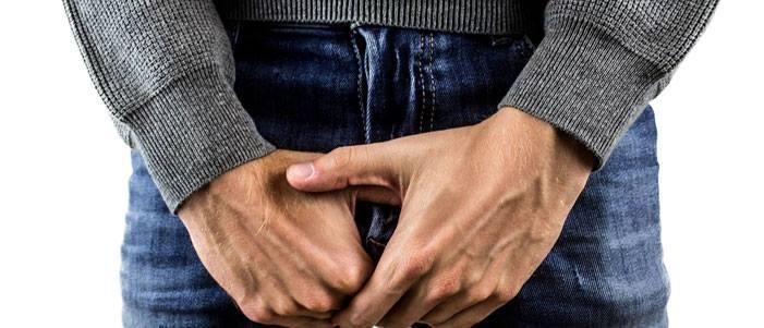 hombre con pantalon de mezclilla sudadera gris tocando su entrepierna por cancer de prostata
