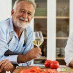 pareja de adultos mayores en su cocina tomando una copa de vino y limpiando verduras