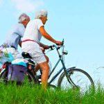 dos adultos mayores hombre y mujer paseando en bicicleta en campo con pasto verde