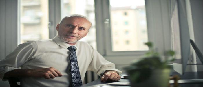 adulto mayor con camisa y corbata sentado frente a computadora y escritorio