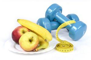 mancuernillas azules, manzanas, plátanos y cinta métrica
