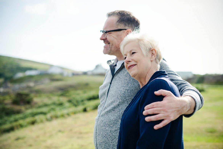 dos personas mayores mujer y hombre abrazados y sonriendo en el campo