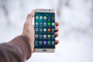 mano sosteniendo un celular que tiene la pantalla encendida