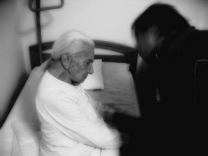 persona mayor sentada con la cabeza agachada y otra persona inclinando a ella