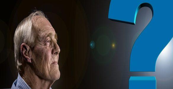 adulto mayor de perfil con fondo negro frente a el un singo de interrogacion color azul