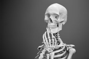 esqueleto blanco con fondo negro en una posición de reflexión