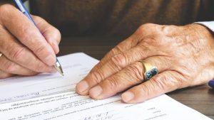 manos de una persona mayor que está firmando un papel
