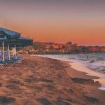 playa camastros y sombrillas azules y cielo rojizo destinos turisticos para adultos mayores