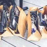 bolsas de compras en el suelo con diferentes artículos en cada una de ellas