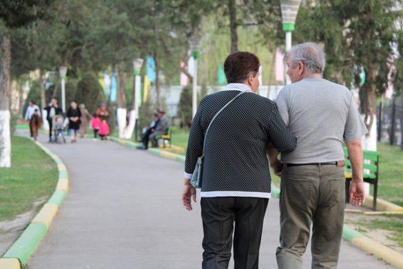 dos personas adultas hombre y mujer tomadas por el brazo caminando en un parque