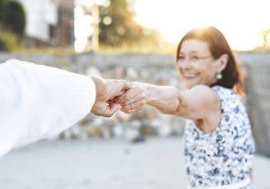 manos de dos personas sosteniéndose, la señora sonríe
