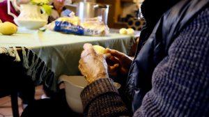 manos de persona mayor sentada limpiando lo que parece una papa s