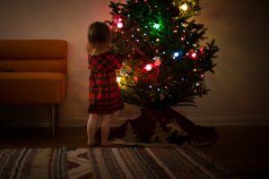 pequeña niña tocando decoraciones de un árbol navideño