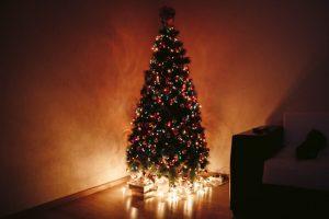 árbol de navidad pequeño y decorado colocado en una esquina