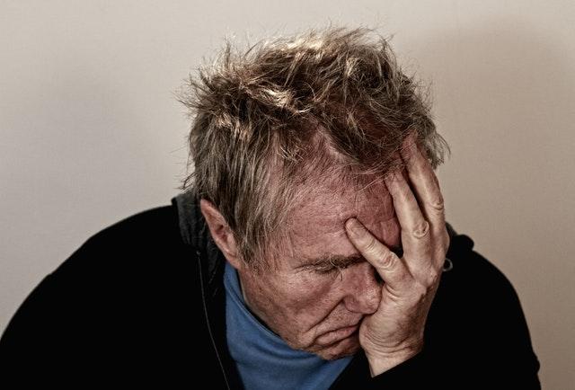 adulto mayor de sueter negro y mano en el rostro descubre las causas del parkinson