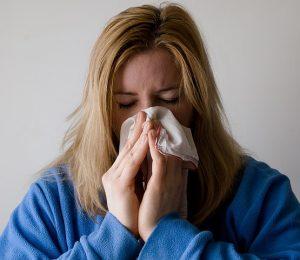mujer con suéter azul sosteniendo un pañuelo desechable sobre su nariz
