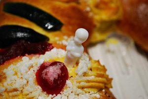 imagen de un trozo de pan conocido como rosca de reyes y saliendo la figura de un muñeco