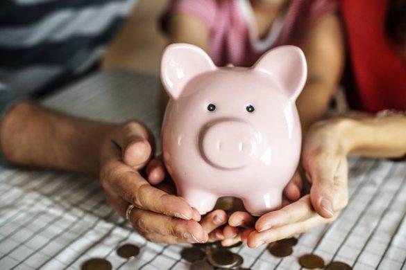manos sosteniendo una alcancía sobre monedas