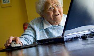 anciana de elntes y canas frente a computadora negra