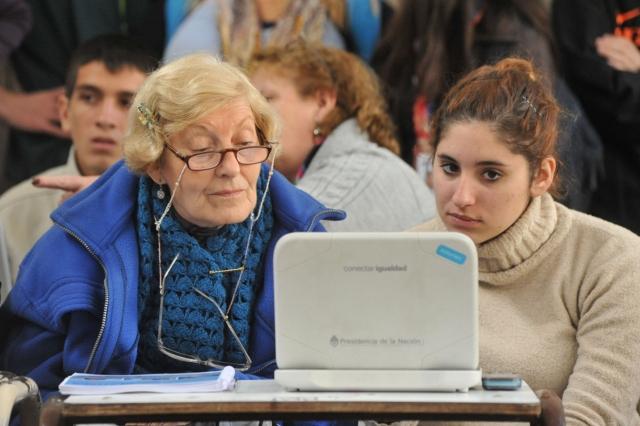 mujer mayor de lentes chamarra azul y mujer joven viendo la pantalla de una computadora