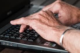 manos de adulto mayor en teclado de computadora