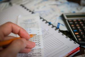 imagen de una libreta, encima un ticket de compra y una mano sosteniendo un lápiz