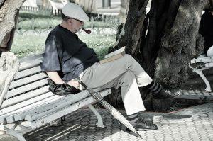 persona sentada en una banca al aire libre leyendo un libro