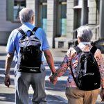 imagen de dos personas mayores tomadas de la mano caminando con dos mochilas en sus espaldas