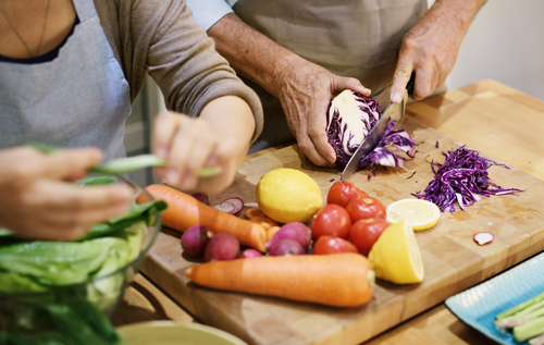 personas adultas cortando diferentes vegetales para su cena