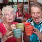 grupo de adultos mayores levantado tazas de diferentes colores